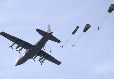 82nd Airborne Division paratroopers jump during the 8th Annual Randy Oler Memorial Operation Toy Drop at Drop Zone Sicily, Fort Bragg, N.C. The Soldiers are donating toys for families of Soldiers and Airmen, as well as orphanages in the local community, in exchange for a chance to make non-tactical parachute jumps with German and Irish military jumpmasters.