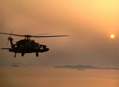 A UH-60 Black Hawk helicopter from 2nd Aviation Battalion, 2nd Infantry Division, flies over the Yellow Sea off the coast of South Korea, during deck-landing qualifications aboard the guided-missile destroyer USS Curtis Wilbur, during Exercise Foal Eagle.
