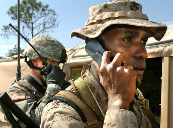 Staff Sgt. Aamir Greene (right), 2nd Marine Division, communicates with pilots using a PRC-117 radio as Staff Sgt. Jimmy Rogers, 1st Cavalry Division, coordinates with a 42-person scout team on a presence patrol in Avon Park, Fla., during Exercise Atlantic Strike III.