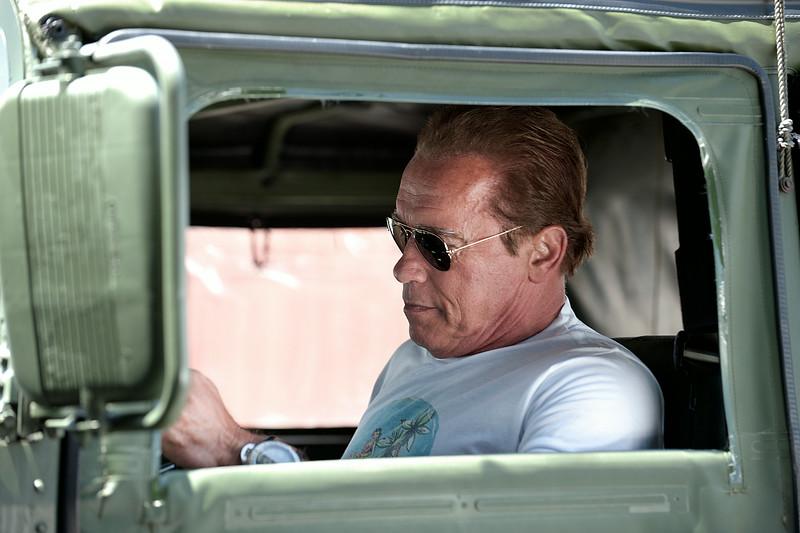 Arnold Schwarzenegger drives his Veggie Hummer