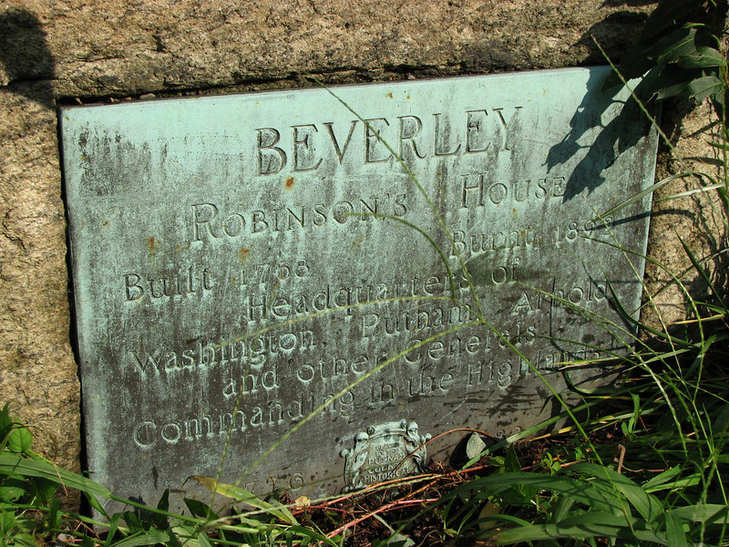 The older bronze plaque set into a fieldstone in the wall along the road.