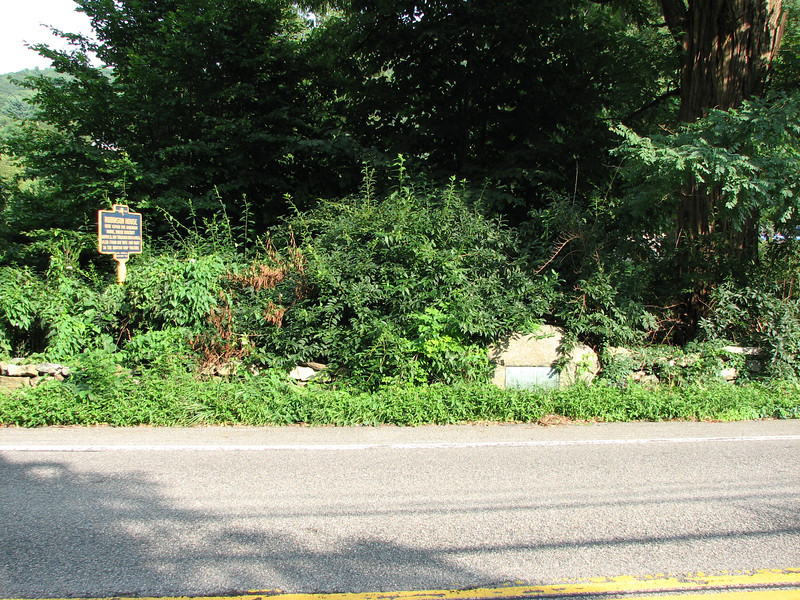Roadside view of the site of the Robinson House. Note the two historical markers, one on a post, and an older bronze plaque set into the stone wall.