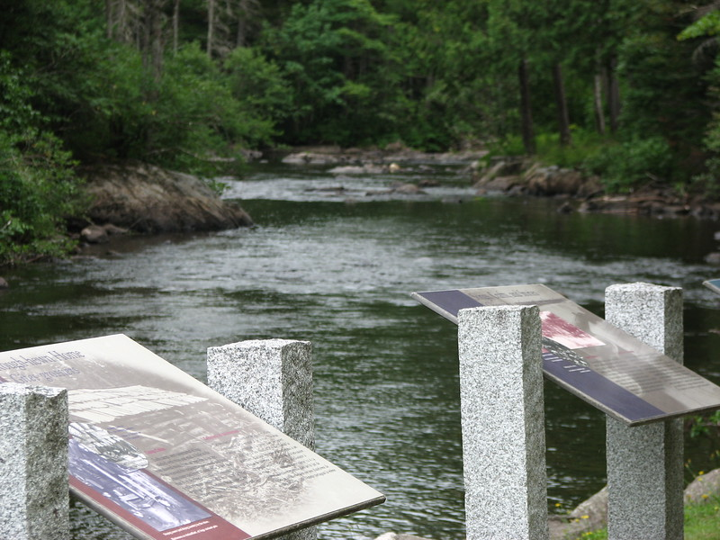 A view downstream, showing other interpretive panels which describe early settlement and logging in the area.