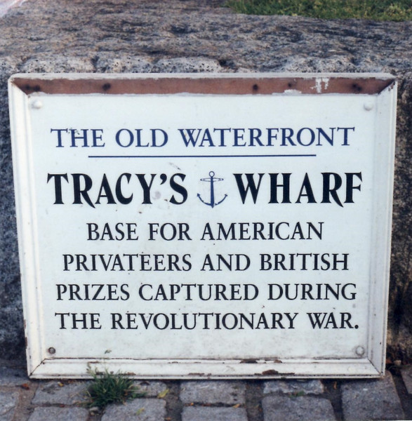 Sign on the low wall along the boardwalk at the site of Tracy's Wharf