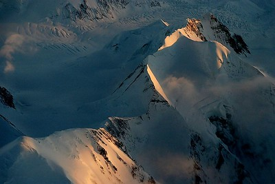 During an early morning flight between Anchorage and Juneau the sun bathes the peaks.
