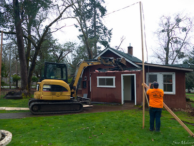Draping the power line over some makeshift poles as they get started with the little backhoe