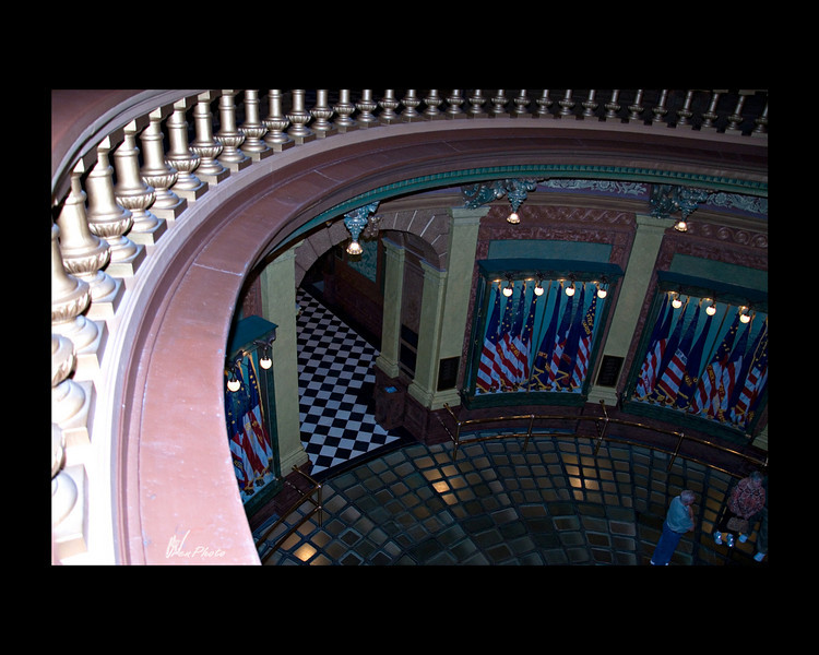 """The rotunda railing from the 2nd floor.<br /> <br /> In the cases circling the rotunda, are 160 replicas of historic battle flags carried by Michigan regiments during the Civil War (1861-1865)<br /> <br /> """"Michigan contributed more than 90,000 volunteers to the struggle to save the Union and abolish slavery, a number which represents more than half of the military-age males in the state at the time. Among the banners in these cases was one carried by the First Michigan Sharpshooters. It was the first Union flag raised over Petersburg, the South's last stronghold, signaling that - after four long and agonizing years - the war was almost over.""""<br /> <br /> (Taken, from""""Your State Capitol"""", booklet.)"""