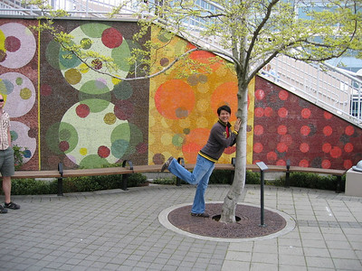 "Christian dances with a tree next to the mural ""Danza del Cerchio"""