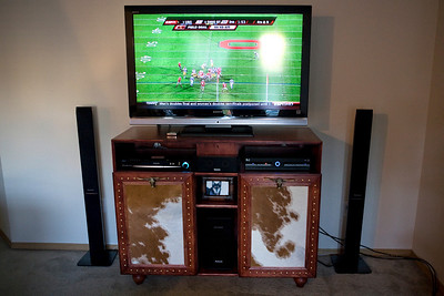 Phil and I needed a new entertainment center, so rather than buy one, we decided to make something that fit our style.  The cowhide was left over from a mirror that we made a few years ago.  I think it turned out pretty great, and I know for a fact that we couldn't buy something like this for what we made it for!  And yep, that's Ohio State playing on the television!  (Even though they lost, we are still big fans!)