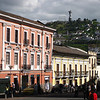 Colourful buildings along calle Cuenca, in front of Church of La Merced, with the statue of the Virgin of Quito behind.