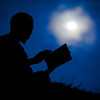 With twilight clinging to the sky and full moon risen, a young Samanzing man reads his new translated bible on a hilltop.