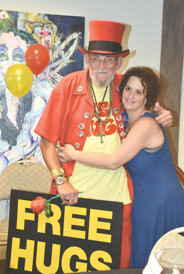 Mindy Harrell, host for the birthday party for Mr. Personality, gets one of his famous free hugs at the party on Saturday.