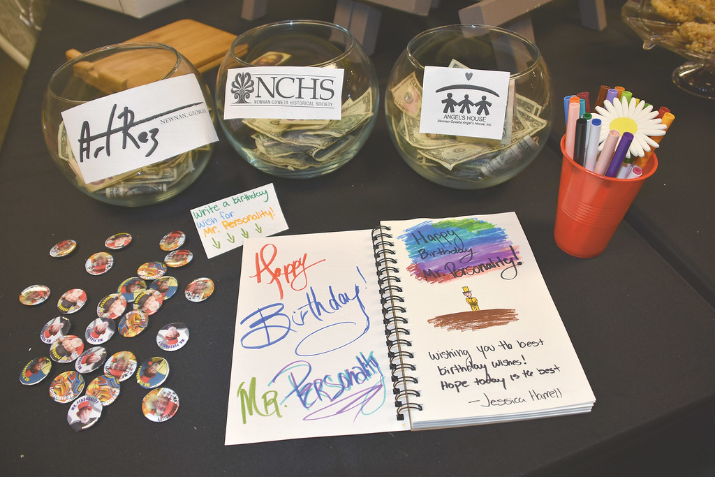 Bowls for donations gather bills and coins at Mr. Personality's birthday bash, while a booklet is filled with greetings from friends and admirers.