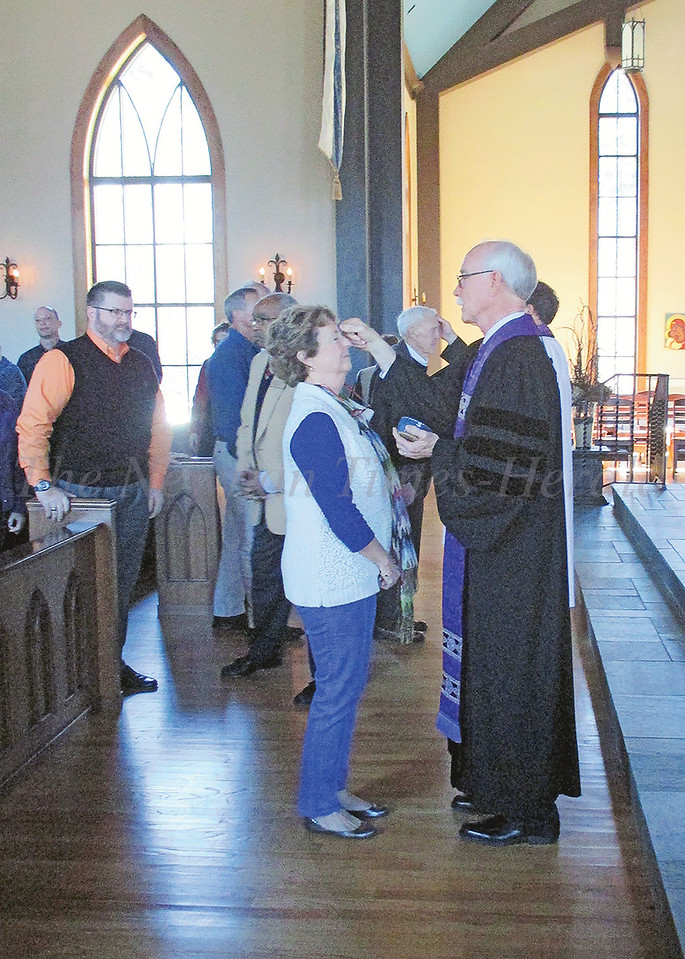 Dr. Joel Richardson makes the sign of the cross on Courtenay Budd's forehead at last year's community Lenten service on Ash Wednesday at St. Paul's Episcopal Church. This year's service is Wednesday at noon at St. Paul's.