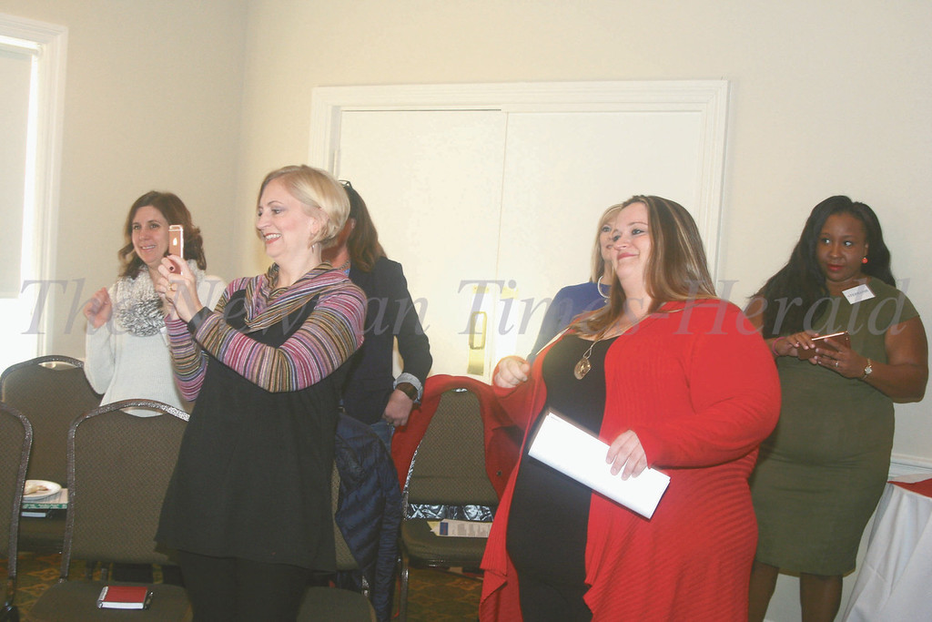 "Mentors stand and ""step,"" into success during an ice breaker at the Stepping into Success Mentorship Program inaugural event on Tuesday at the Newnan Country Club."
