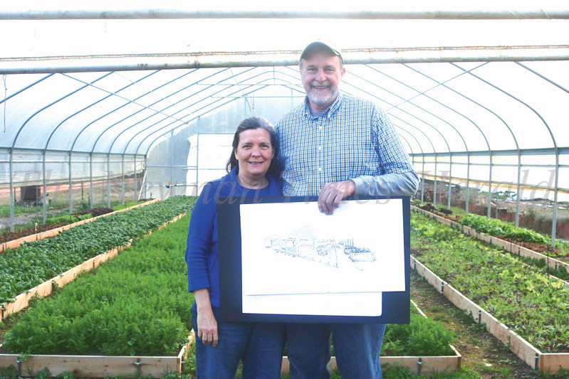Judy Cunningham (left) and Mike Cunningham (right) hold a sketch of a teaching pavilion they are raising money to complete by the summer at their farm on Highway 154 in Newnan.