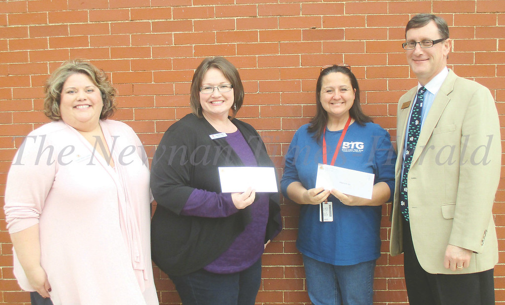 Ginger Jackson-Queener, left, and Walter Jones, right, present Fill the Stocking checks to Alison Wallace, second from left, and Heather Creech. The funds went to Bridging the Gap, the Salvation Army and Toys for Tots.