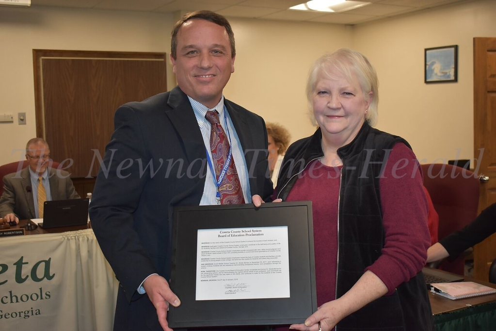 Arnall Middle School Principal Patrick Sullivan, left, presents a proclamation from the Coweta County Board of Education to Dr. Sheila Barnes, right.