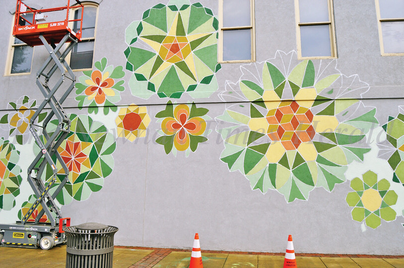 Artist Molly Rose Freeman's locally-inspired, floral-like mural, located on the side of a downtown building along West Court Street is in-progress Saturday afternoon. The newest artist-in-residence's work has locals excited to see the complete mural.