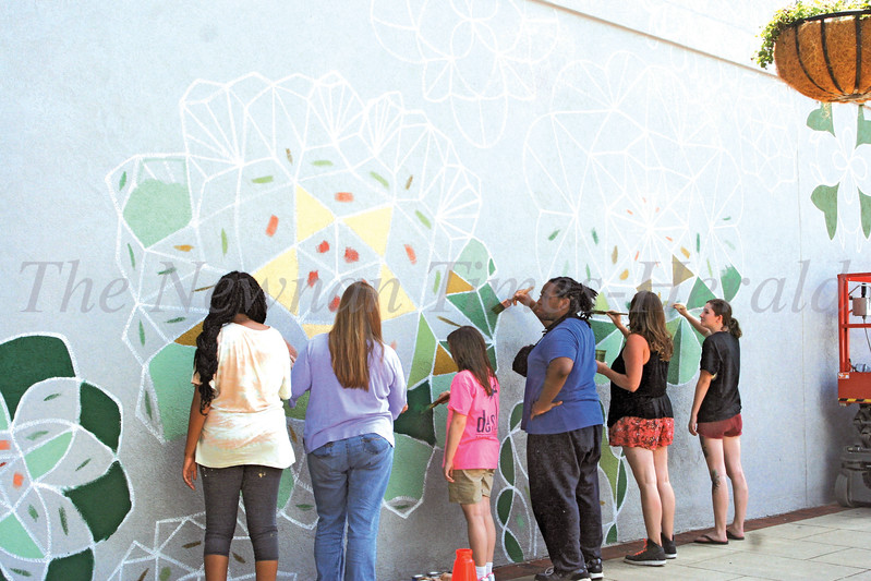 Molly Rose Freeman, artist-in-residence, is painting a mural of geometric flowers along with some University of West Georgia students and guests at the Alamo in downtown Newnan. Freeman started on the mural Monday and hopes to be finished with the project the first week of August.