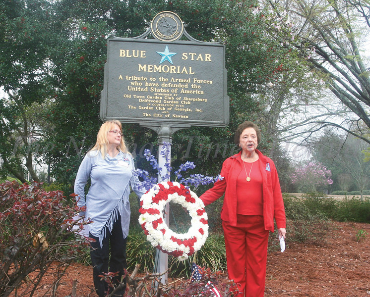 Carla Krajna-Kan, president Old Town Garden Club of Sharpsburg, left, and Martha Price, president of The Garden Club of Georgia, Inc., right, dedicate the Blue Star Memorial Marker yesterday at the Veterans Memorial Plaza at the city park at Jackson Street and Temple Avenue.