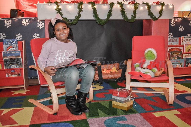 "Jasmine Beavers is ready for Santa as she sits by Elm Street Elementary's fireplace display reading ""Twas The Night Before Christmas"" to the Grinch in the school library."
