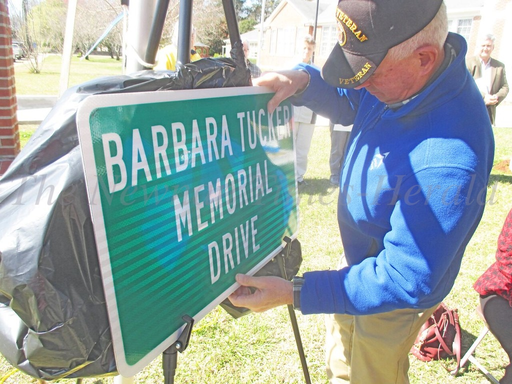 Grantville City Manager, Al Grieshaber, unveils one of the signs that will be placed on LaGrange Street, designating it as Barbara Tucker Memorial Drive