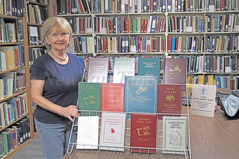 Ted O. Brooke recently donated a number of geneology books to the Geneology Society of Newnan.  Dianne Webb, Publicity Chairman for the society displays the collection at the library.