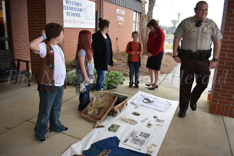 Students and teacher from Western Elementary look on the items retrieved from the time capsule fifth graders buried in 1993.