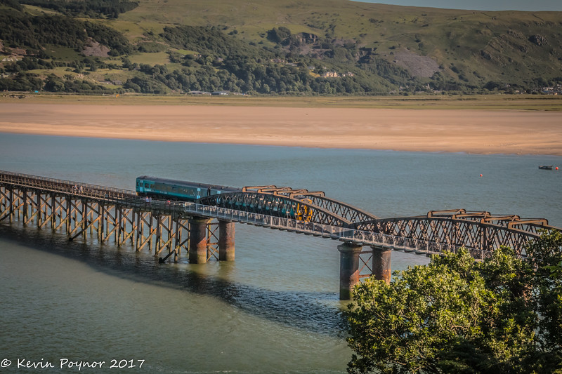 Barmouth Rail and pedestrian bridge. ArrivaWales Train Class 158 passing over the final section into Barmouth