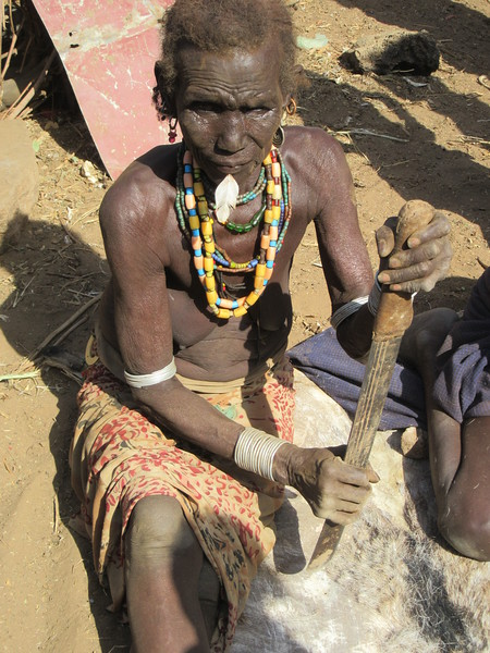 825_Omo Valley  Dassenech Village  Elder Woman working on a piece of Leather (goat)