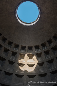 The oculus of the Pantheon in Rome. It allows the rain to enter and fall to the floor, where it is carried away through drains. Moreover it makes the structure of the dome lighter together with its coffers and the use of lighter materials on the top. It is worth considering that almost two thousand years after it was built, Pantheon's dome is still the world's largest unreinforced concrete dome. It is a monument where the beauty of geometry meets beauty of art. For example the height to the oculus and the diameter of the interior circle are the same, 43 meters