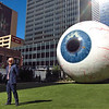 Artist Tony Tasset standing in front of his Eye sculpture