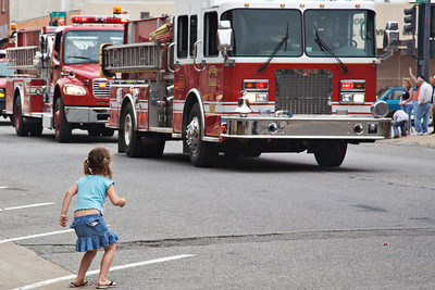 This little girl would very much like to dash out to pick up the candy which was thrown from the parade floats.  She is somewhat put off by the big red trucks with sirens blaring and lights flashing.  Armed Forces day parade.  McAlester, Oklahoma.  May 5th, 2007