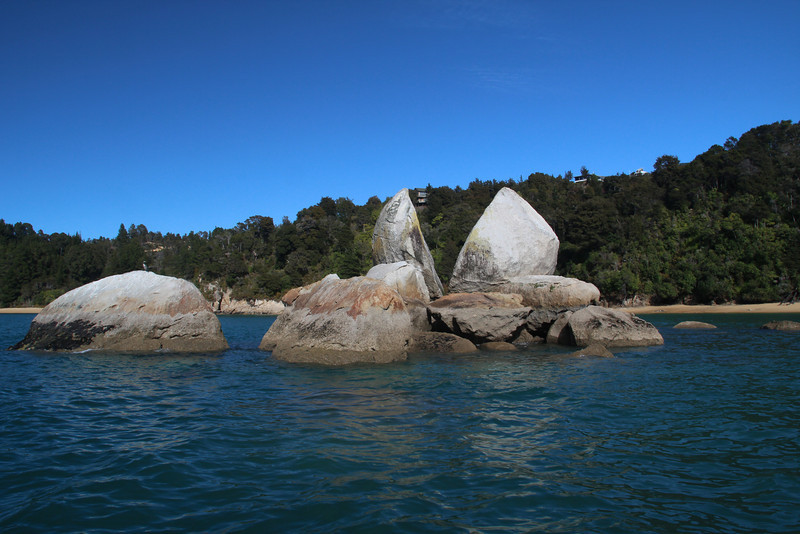 Split Apple Rock. This rock was used as a logo for apples exported from New Zealand for a number of years. In high tide, kayakers could paddle through the middle.