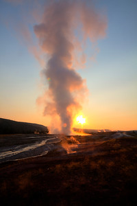 Old Faithful erupting during sunrise