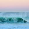 a surfer and a wave meet dawn