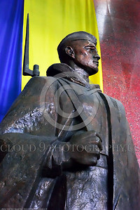 KIEV WWII MUSEUM 0009 A side view of a proud heroic focused steadfast Ukrainian soldier with bayonet statue before colorful Ukrainian flag, statue picture by Peter J  Mancus