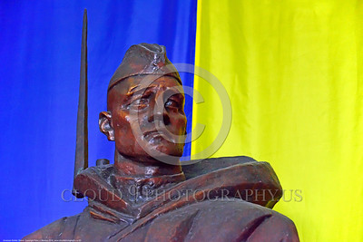 Ukrainian Soldier Statue 03 A quarter front view of a proud heroic focused steadfast Ukrainian soldier with bayonet statue before colorful Ukrainian flag, statue picture by Peter J  Mancus