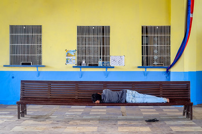 A man catches an afternoon nap at the train station in Kampot, Cambodia. January 2017.