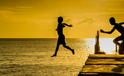 A couple of kids jumping off a pier as the sun goes down in Sihanoukville, Cambodia. January 2017.