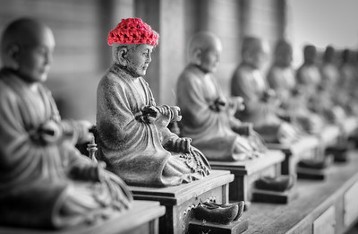 Patrons of the temple knit scarves and hats to protect the Buddha statues during colder weather. This one was 15 cm tall. Japan. April 2017.