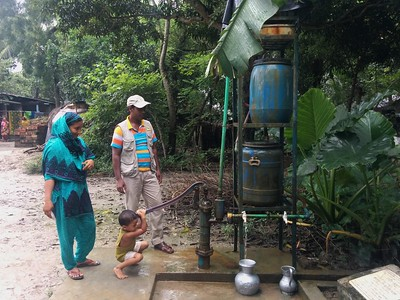 Family collecting water from a smaller community safe drinking water device. Photo credit: R. Reddy