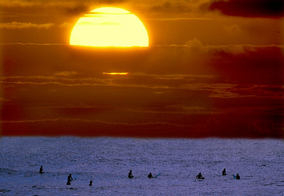 Surfers silhouettes at sunset at Sunset Beach on the North Shore of Oahu, Hawaii