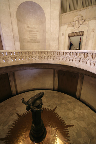 "ANZAC War Memorial, Sydney. Interior view, facing the northeast. At top right is the vestibule housing the Eternal Flame. The Memorial's focal point is the monumental bronze figure by Rayner Hoff entitled ""Sacrifice"", shown at bottom left."