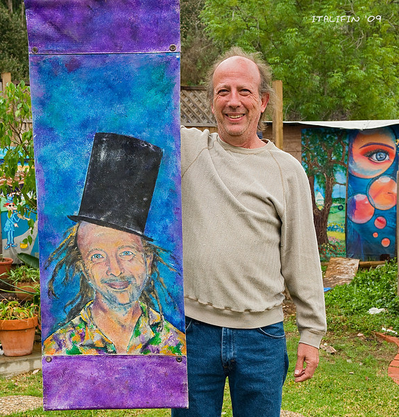 "Organizer Danny Salzhandler, president of the 101 Artists Colony,  shows off some of his personal collection of banners including one made in his likeness.  Danny is a sculptor who lives in Cardiff and specializes in ""Biosculptures""."