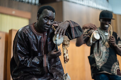 Pape Diouf and Arouna Diarra playing talking drums, 2018