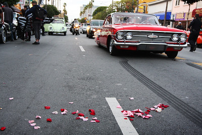 Mission Street SF, 3/21/15 – Dozens of Low Riders and strewn flower petals blow by the Mission Cultural Center where friends, family and supporters gathered to commorate the 1st anniversary of Alex Nieto's death.
