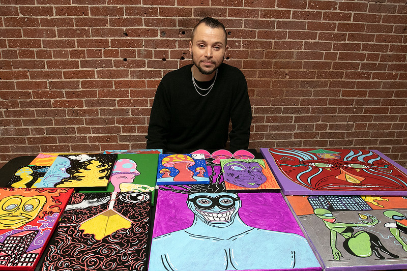 The first Art haul was held at Strong Style Coffee in Fitchburg on Saturday, Jan. 4, 2020. Ryan Schneider of Fitchburg sits with his artwork he had on display at the show. SENTINEL & ENTERPRISE/JOHN LOVE