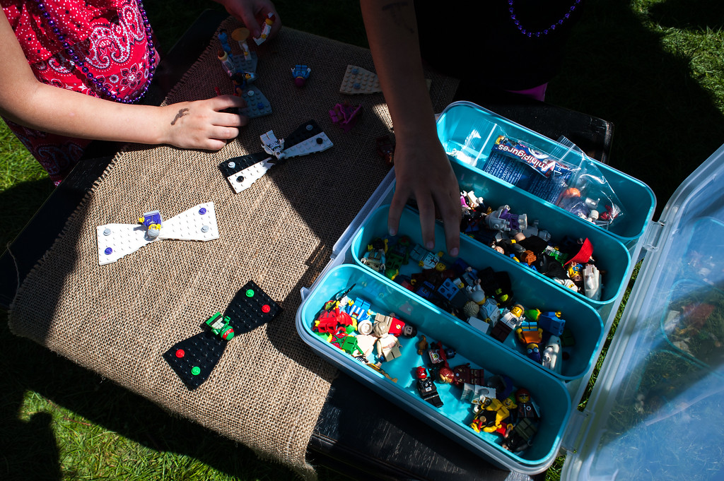 . Sisters Etta Bassett, 4, left, and Harper Bassett, 6, search through a box of Lego blocks to make bow ties at the Son and Pop Bowtie Shop during Art in the Park in North Lake Park Sunday, August 13.